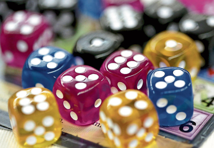 """Colorful dice lie on a playing card at the new product presentation at the """"Spiel '19"""" trade fair.  Dice take up hardly any space in the suitcase and can be used for a lot of games.  Photo: Roland Weihrauch"""